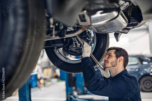 plakat Auto car repair service center. Mechanic examining car suspension