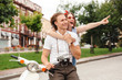 Cheerful young lovely couple posing together with retro scooter