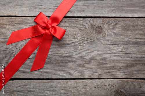 Fotografia  Red bow with ribbon on grey wooden table