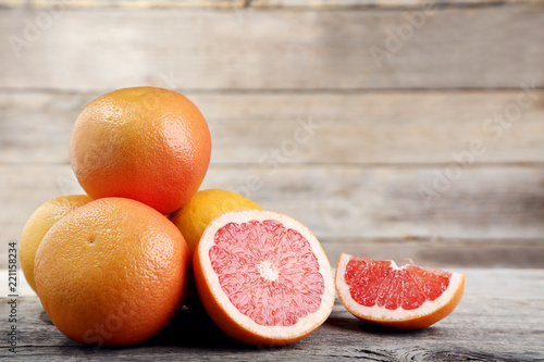 Ripe grapefruits on grey wooden table