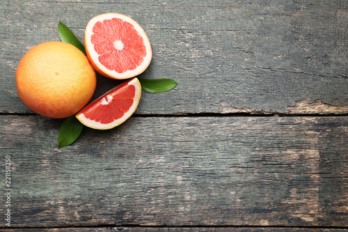 Ripe grapefruits with green leafs on grey wooden table