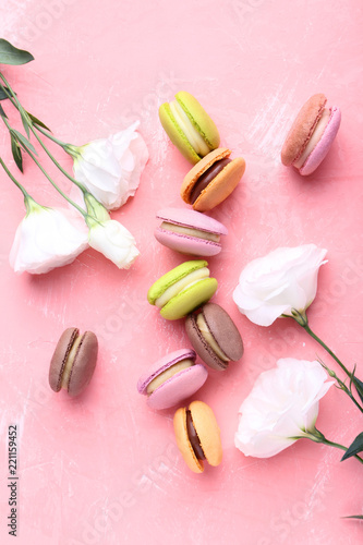 Colorful macarons with eustoma flowers on pink background