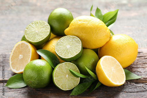 Lemons and limes with green leafs on grey wooden table