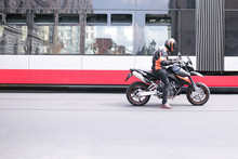 Portrait Of A Motorcyclist Standing On A Traffic Light On The Background Of A Tram. A Man In A Helmet And A Sports Motorcycle Is In The Background Of Public Transport