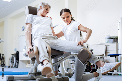 Fototapety, obrazy: Professional help. Calm cheerful experienced doctor in a rehabilitation center touching the knee of her aged disabled patient while helping him to overcome his pain