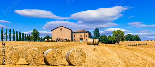 Beautiful countryside landscape with hay rolls and farm houses in Tuscany. Italy