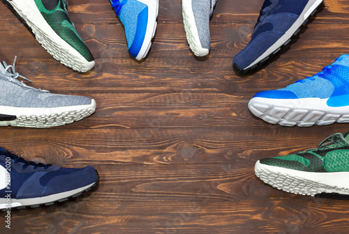 Fotografija  Top view shop display of unbranded modern new stylish sneakers running shoes for men on wooden background texture with copy space