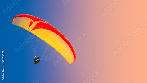 Beautiful yellow and red paraglider flying in colorful sky