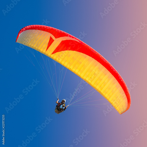 Foto op Canvas Luchtsport Beautiful yellow and red paraglider flying in colorful sky