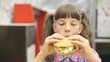 Caucasian teen girl eating hamburger for Breakfast at school.