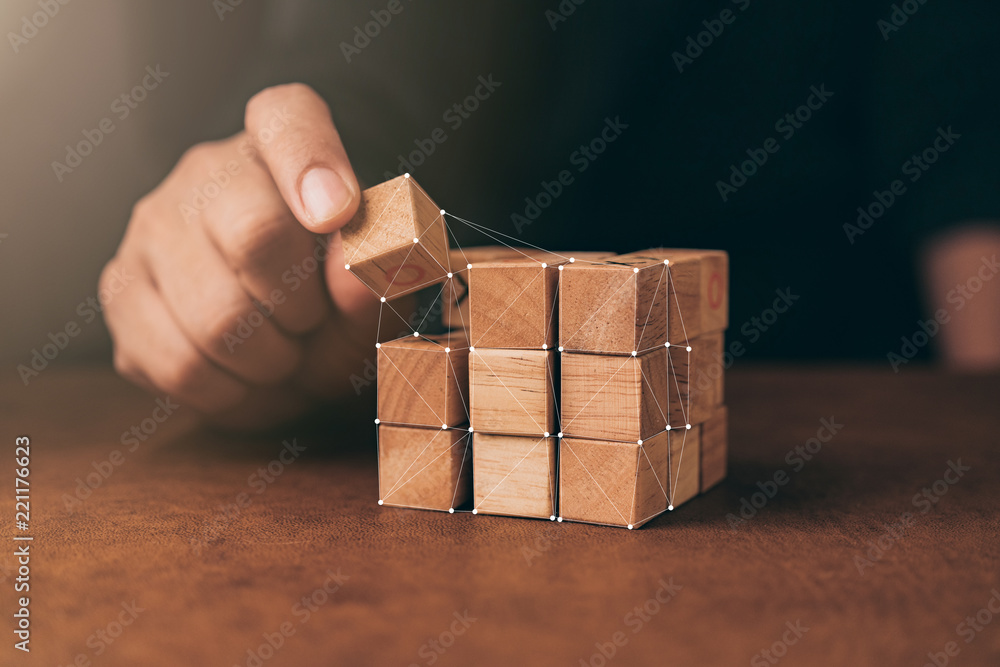 Fototapeta business man try to build wood block on wooden table and blur background business organization startup concept