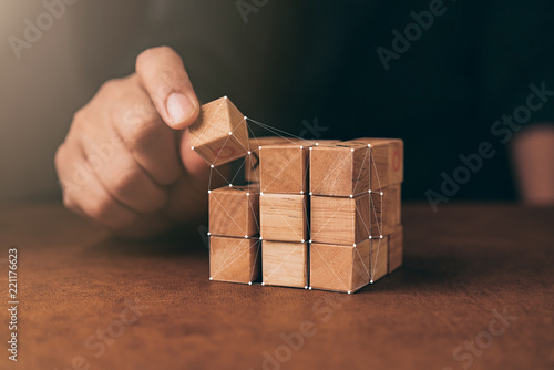 Tela business man try to build wood block on wooden table and blur background busines