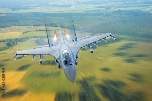 Valokuva Combat fighter jet on a military mission with weapons - rockets, bombs, weapons on wings, at high speed with fire afterburner engine nozzles, flies over the terrain
