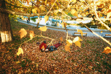 Top Side View Young Couple In Love Woman Man In Casual Warm Clothes Holding Hands Looking At Each Other Lying On Fallen Leaves In Autumn City Park Outdoors. Love Relationship Family Lifestyle Concept.