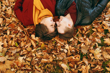 Top View Portrait Of Young Happy Smiling Couple In Love Woman, Man With Closed Eyes Facing Each Other Lying On Fallen Leaves In Autumn City Park Outdoors. Love Relationship Family Lifestyle Concept.