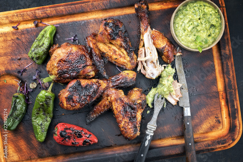 Foto Traditional Caribbean barbecue jerk chicken wings and drumsticks with chimichurr