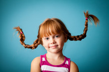 Happy Little Girl With Pigtails, Isolated On Teal
