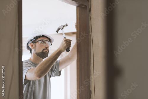 Fototapeta Carpenter installing a door jamb at home