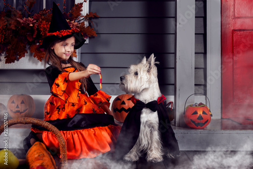 Young funny girl child kid in halloween orange costume playing outdoor with spoo Fototapeta