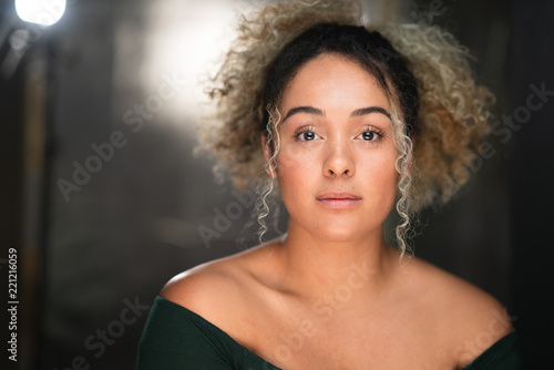 Photo  Headshot of young woman with curly hair