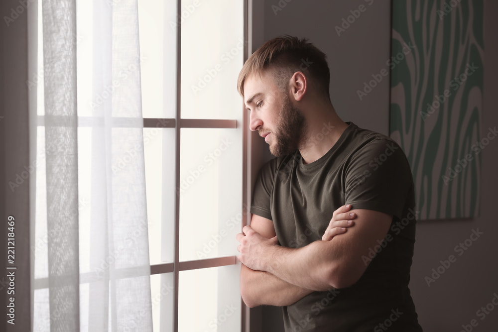 Fototapety, obrazy: Depressed young man near window at home