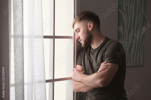 Depressed young man near window at home Fototapeta