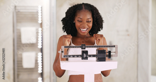 Fotografía  Beautiful black woman happily weighs herself on scale in bathroom