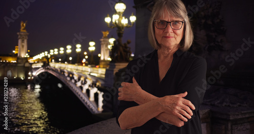 Lovely mature woman with stern look crossing arms by Pont Alexandre III in Paris Fotobehang