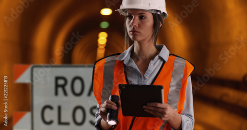 Canvas Print female worker shining flashlight at camera while in tunnel under construction