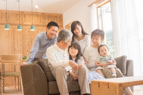 Valokuva  リビングのソファで微笑む3世代家族