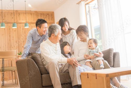 Fotografija リビングのソファで微笑む3世代家族