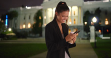 Young Female Professional Texts Using Cell Phone While Smiling At Night