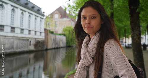Poster Brugge Beautiful woman in striped scarf by canal in Bruges Belgium making eye contact