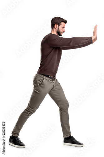 Fotomural  A bearded man in casual clothes tries to push a heavy object with both arms with one leg put in front for balance