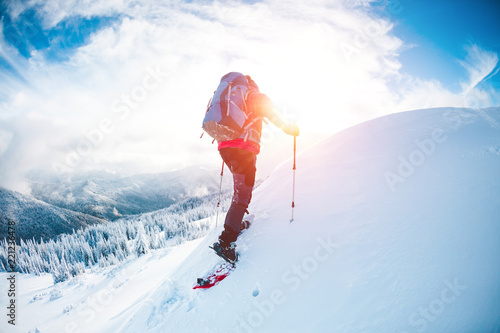 Poster de jardin Alpinisme A man in snowshoes in the mountains in the winter.