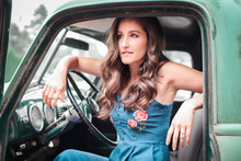 A  Beautiful Young Woman Sitting In An Old Classic Pickup Truck
