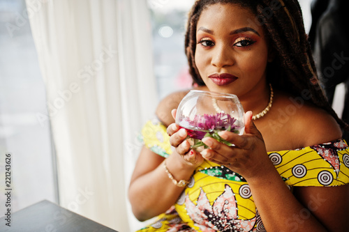 Cute small height african american girl with dreadlocks, wear at coloured yellow dress, sitting at cafe with flower at glass.