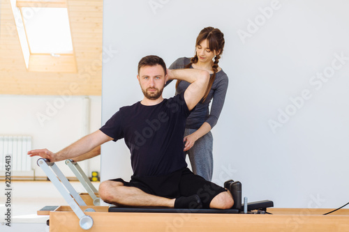 Brunette female instructor with cute two braids hairstyle consulting hansdome beard man workout pilates on reformer practice in pilates studio, working out indoor, correcting beginners, full length Fototapet