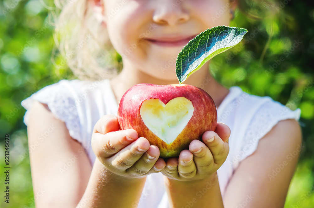 Fototapeta Child with an apple. Selective focus. Garden.