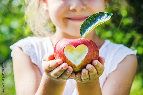 Valokuva  Child with an apple. Selective focus. Garden.
