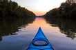 Bow of blue kayak on Danube river at dusk. Kayaking on calm autumn river in the evening. View on river from the bow of kayak
