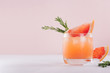 canvas print picture - Refreshing cold citrus cocktail with ice cubes, green rosemary and slice grapefruit on soft light pink and white background.