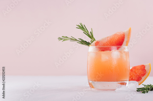 Refreshing cold citrus cocktail with ice cubes, green rosemary and slice grapefruit on soft light pink and white background.