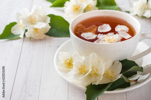Photo Mug of herbal tea with petals of Jasmine flowers on a light background