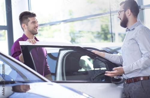 Fotografie, Obraz  Putative buyer talking to a car dealer next to a car