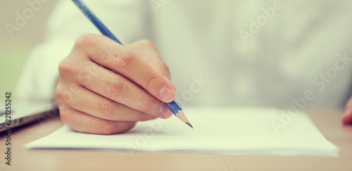 close up student man hand using pencil for doing text exam