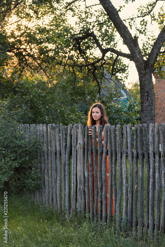 Fotografie, Obraz  a sad expectant girl stands behind a wooden palisade in a village attire