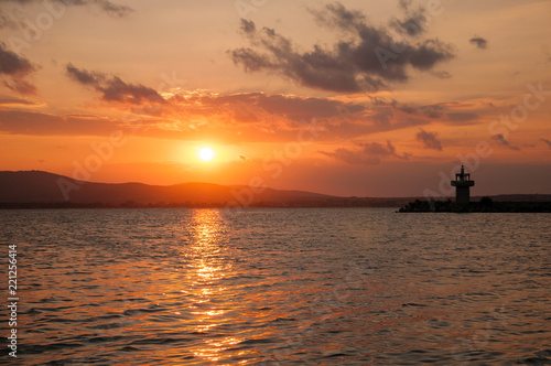 Lighthouse against a beautiful evening sunset on the sea. Amazing sunset on black sea and beautiful cloudscape.