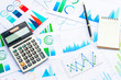 Calculator and Pen on Business Graphs finance document.