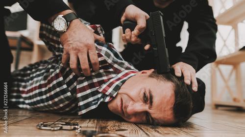 Fotografie, Tablou  Policeman Put A Gun To The Head Of The Criminal.